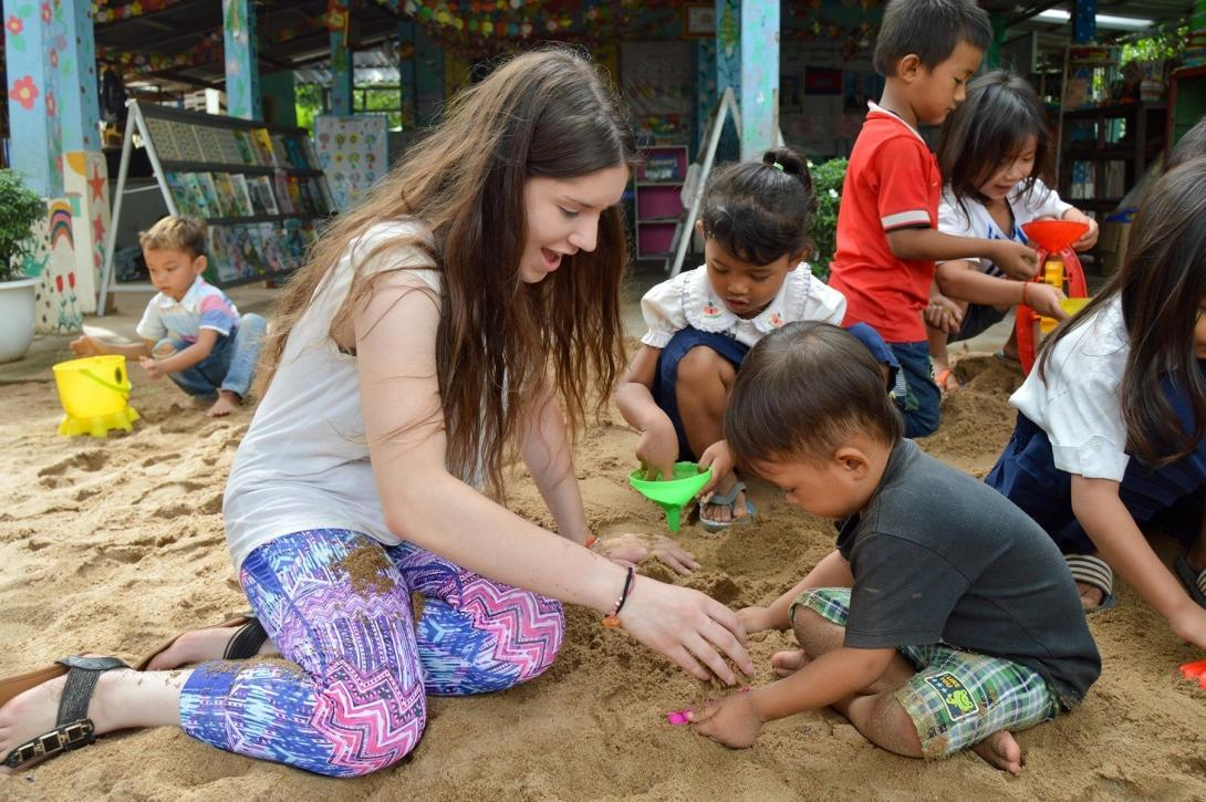 A Care volunteer and children playing together in a sand pit